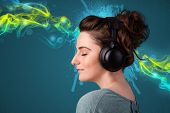Pretty young woman with headphones listening to music, glowing smoke concept