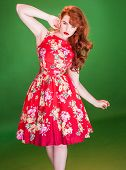 Red haired beautiful young woman, wearing a red summer dress with floral print, while posing with a wild and ingenuous facial expression, on green