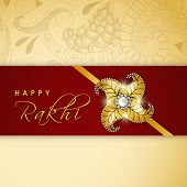 Shiny golden rakhi on floral decorated maroon and beige background for Happy Raksha Bandhan celebrat