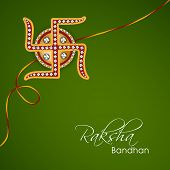 Beautiful rakhi decorated with Swastik on green background for Happy Raksha Bandhan celebrations.