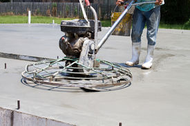 picture of slab  - Construction worker uses a motorized power trowel to smooth and finish a concrete slab at a new home job site - JPG