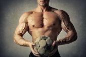 Muscular man holding a soccer ball