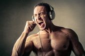 Muscular man listening to music
