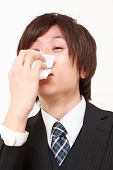 stock photo of sneezing  - businessman with an allergy sneezing into tissue - JPG