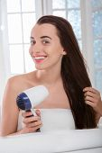 Woman drying hair with hairdryer