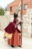 Actress in medieval dress standing near a pole