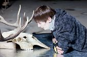 picture of black tail deer  - Young man lying down looking at the deer skull in a dark - JPG
