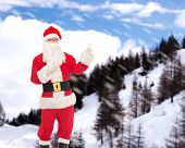 christmas, holidays, gesture and people concept - man in costume of santa claus pointing fingers over snowy mountains background