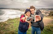Young couple taking selfie photo with smartphone outdoors in a cold day