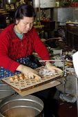 SAN FRANCISCO- MARCH 20: An asian woman bakes fortune cookies in a Chinatown factory in San Francisc