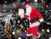 christmas, holidays and people concept - man in costume of santa claus running with clock showing twelve over snowy night city background