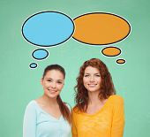 school, education, communication and people concept - smiling student girls over green board background with text bubbles