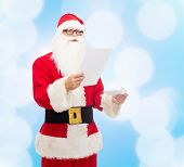 christmas, holidays and people concept - man in costume of santa claus reading letter over blue lights background