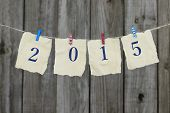Year 2015 in blue on antique paper sign by wooden background