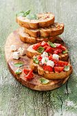 Bruschetta With Chopped Tomatoes, Basil And Cheese On Grilled Crusty Bread