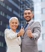 business, partnership, success, gesture and people concept - smiling businessman and businesswoman showing thumbs up over office building