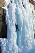 Man climbing frozen waterfall
