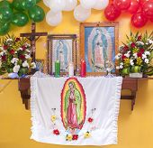 stock photo of guadalupe  - Beautifully decorated altar with flowers religious objects and balloons in Mexican flag colors to commemorate the apparition of Our Lady of Guadalupe - JPG