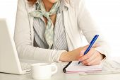 A woman at the desk writting on a paper, isolated on white