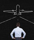 Businessman Looking At Airplane