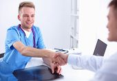 Doctor shaking hands with a patient, sitting on the desk in office