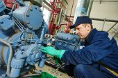 service engineer worker at industrial compressor refrigeration station repairing and adjusting equipment at manufacturing factory