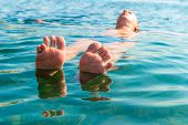 Feet With Splayed Fingers Lying On The Water Man