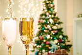 Two Champagne Glasses On Defocused Background Living Room With Christmas Tree