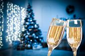 Two Champagne Glasses On Defocused Background Living Room With Christmas Tree. Blue Toned