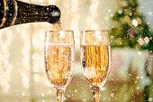 Two Champagne Glass With Stars And Snow On Defocused Background Living Room With Christmas Tree