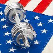 Metal Dumbbell Over Us Flag As Symbol Of Healthy Nation - Studio Shot