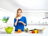 Young and beautiful housewife woman cooking in a kitchen