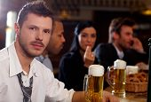 Portrait of casual young businessman drinking beer in pub, looking at camera.