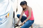 picture of arabic woman  - Closeup portrait young woman in pink tanktop and blue jeans fixing flat tire with jack and tire iron isolated green trees and road outside background - JPG