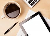 Tablet pc with copy space and a cup of coffee on a wooden work table close-up