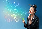 Pretty lady blowing big colorful bubbles on blue background