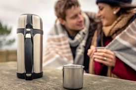 pic of thermos  - Closeup of metalic cup and thermos with hot beverage in a wooden table with young couple under blanket blurred on the background - JPG