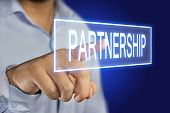 pic of partnership  - Business concept image of a businessman clicking Partnership button on virtual screen over blue background - JPG