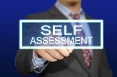 image of self assessment  - Business concept image of a businessman clicking Self Assessment button on virtual screen over blue background - JPG