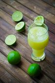 foto of lime  - green limes with lime juice in the glass on the table - JPG