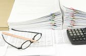 stock photo of spectacles  - Brown pencil on spectacles and calculator have pile of paperwork as background - JPG