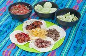 picture of condiment  - Taco plate display of four corn tortillas with different kinds of barbecued meat and onion with condiment bowls of fresh Mexican salsa cucumbers and limes on a decorative blue tablecloth - JPG