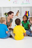 image of storytime  - a preschool teacher reading children books in storytime in classroom - JPG