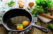 image of nettle  - Scrambled eggs with nettles in a pan on a wooden table - JPG