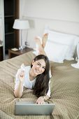foto of laying-in-bed  - Young woman laying in the bed and shopping online - JPG