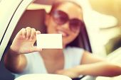 pic of driver  - woman driver sit in car hold one blank business card - JPG