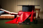 Graduation Cap And Red Ribbon Lying On Book At Library poster