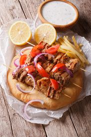 foto of souvlaki  - Greek souvlaki kebab with tomatoes onions and french fries on pita bread close - JPG