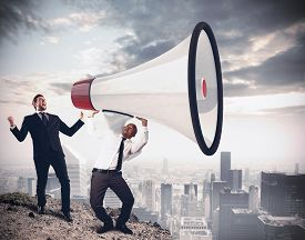 stock photo of shout  - Businessman shouting into megaphone over the city - JPG