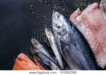 poster of Variety of raw fresh fish. Whole tuna and herring, fillet of salmon, cod, red fish on crushed ice over dark wet metal background. Top view with space. Fish market concept